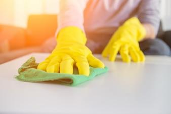 Pessoas, tarefas domésticas e conceito de arrumação - close up of man hands cleaning table with cloth in home