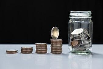 Pilhas de moedas e vidro para investimento no futuro