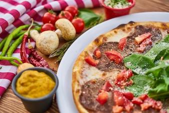 Pizza italiana com vegetais e mostarda na mesa de madeira
