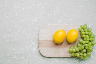 Placa de corte com cacho de uvas e limões