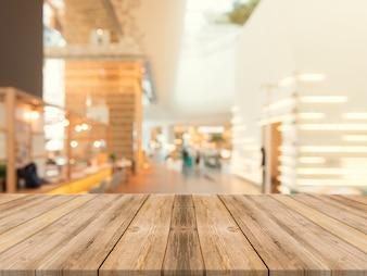 Placa de madeira em cima da mesa vazia de fundo desfocado. Perspectiva mesa de madeira marrom sobre borrão no fundo da cafeteria - pode ser usado maquete para exibição de produtos de montagem ou layout visual chave de design.