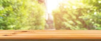 Placa de madeira tabela vazia fundo borrado. Perspectiva mesa de madeira marrom sobre borrão árvores fundo da floresta - pode ser usado mock para exibição ou montagem de seus produtos. temporada de primavera. Banner panorâmico.