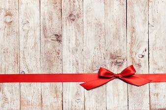 Placas de madeira com um laço vermelho