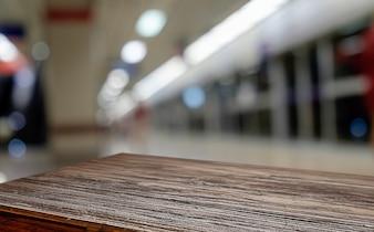 Plataforma de espaço de mesa de madeira vazia e cafetaria borrada onde o fundo de trabalho e de encontro para montagem de exibição de produtos. Foco seletivo.