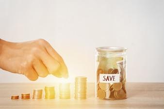Poupar dinheiro, mão colocar pilha de moedas na escadaria do dinheiro, conceito de economia e economia de negócios