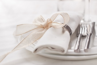 Prato com talheres e um guardanapo com um arco