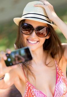 Pretty young girl que toma selfies com seu telefone inteligente no jardim.