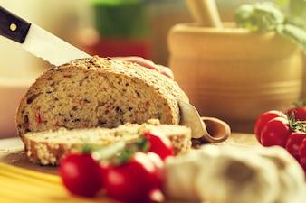 Processo de corte pão integral na cozinha. Fundo Da Cozinha. Processo de cozimento. Tonificado.