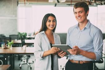Profissionais alegres que usam a tecnologia no trabalho