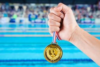 Punhado de homem asiático segurando medalha de ouro com fundo borrado de piscina.