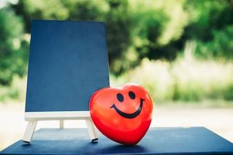 Quadro de giz com coração vermelho de sorriso no fundo da natureza.