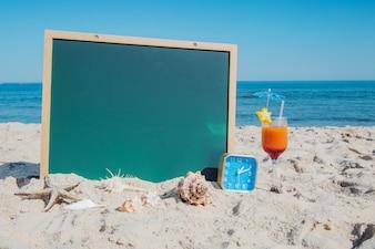Quadro-negro e cocktail na praia