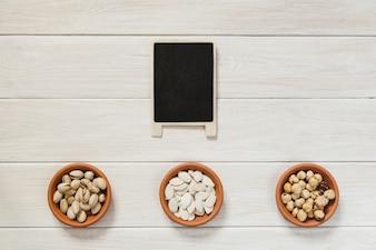 Quadro-negro e tigelas com nozes e sementes