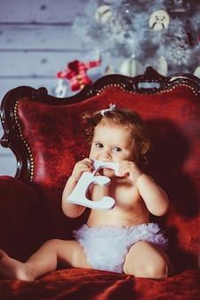 """""""Criança pequena sentada na poltrona"""""""