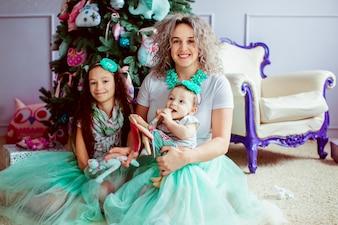 """""""Mãe e filhas sentadas no chão"""""""