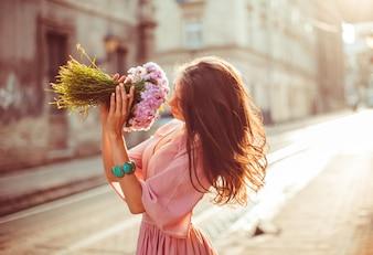 """""""Menina cheirando flores de pé na rua"""""""