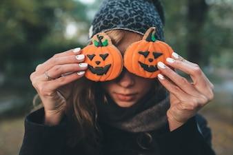 """""""Mulher que fecha o rosto com biscoitos de Halloween"""""""