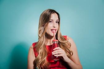 Rapariga loira bebendo suco vermelho