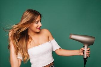 Rapariga loira e secador de cabelo