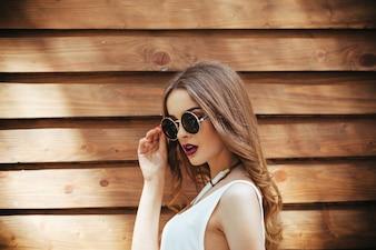Rapariga no t-shirt branco posando com fundo de madeira