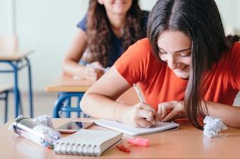 Rapariga rindo e escrevendo