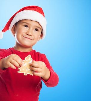 Rapaz pequeno com uma árvore bolinho