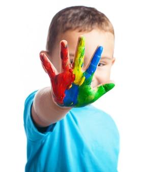 Rapaz pequeno com uma mão cheia de tinta cobrindo o rosto