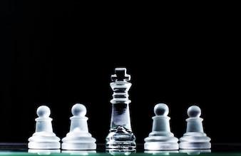 Rei e vários peões no tabuleiro de xadrez em fundo escuro. Conceito hierárquico.