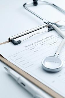 Relatório de exame médico e estetoscópio no desktop branco
