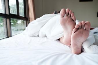 Relaxe os pés na cama.