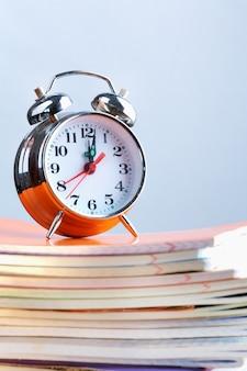Relógio em uma pilha de cadernos