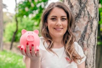 Retrato de close-up feliz, mulher de negócios sorridente, segurando cofrinho, isolado ao ar livre fundo de árvores verdes. Economia financeira, conceito bancário. Emoções positivas, expressões faciais