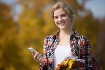 Retrato de estudante externo, segurando o telefone móvel em uma mão