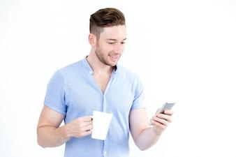 Retrato de homem feliz com copo usando smartphone
