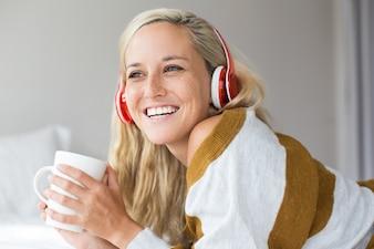 Retrato de jovem mulher em fones de ouvido rindo