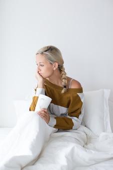 Retrato de mulher jovem e perturbada tomando chá na cama