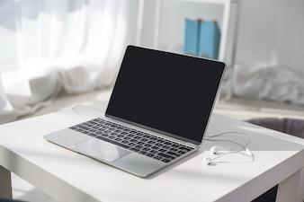Retrato de still-life do computador, caneta, caneca de café na mesa, lâmpada e plantas em um ambiente luminoso.