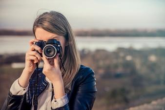Retrato de um fotógrafo que cobre seu rosto com a câmera. Ph