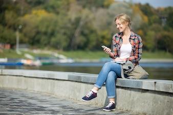Retrato de uma jovem atraente sentada na ponte