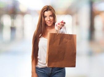 Retrato de uma jovem mulher segurando um saco de compras