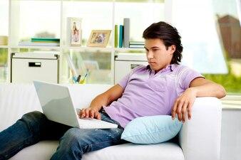 Retrato do homem conforto de utilização laptop