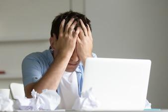 Retrato do homem perto do laptop, as mãos fechando o rosto