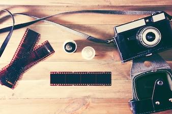 Retro câmera vintage e filme fotográfico em fundo de madeira