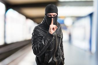 Robber fazendo um gesto de silêncio