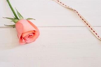 Rosa e renda branca e vermelha sobre uma mesa de madeira