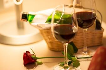 Rosa vermelha com dois copos de vinho
