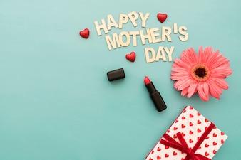 """Rotulação do """"dia feliz mãe"""" com batom, caixa de presente e flor"""