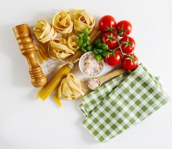 Saboroso colorido conceito de comida italiana fresca com várias massas espaguete, manjericão fresco, tomate, especiarias. Conceito Cozinhando.