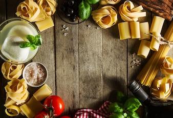 Saboroso colorido fresco conceito de comida italiana com várias massas espaguete, queijo mozzarella, manjericão fresco, tomate, azeite, especiarias. Conceito Cozinhando. Local para Texto.