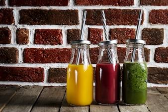Saborosos smoothies caseiros frescos coloridos em frascos de vidro na mesa de madeira. Fundo Da Cozinha.